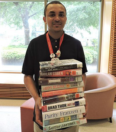 Staff member holding a large stack of books