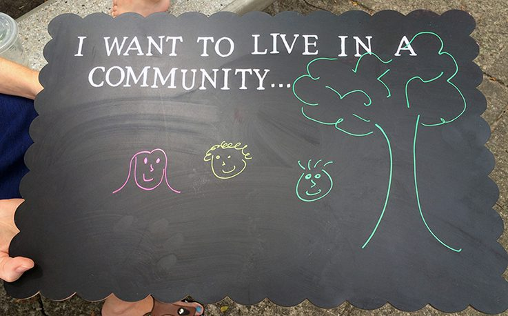 "Chalkboard with ""I want to live in a community..."" written at the top and a chalk drawing of a tree and smiling faces"