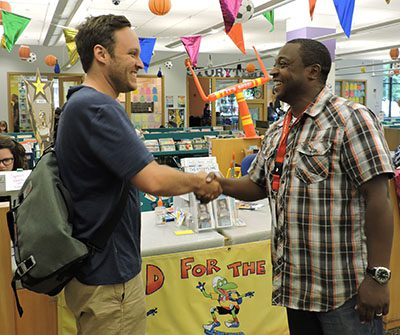 olmes Elementary teacher Drew Finkbeiner and Oak Park Public Library's Rob Simmons shaking hands.