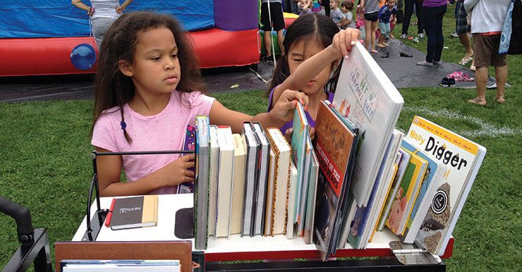 Two girls selecting books from the Book Bike