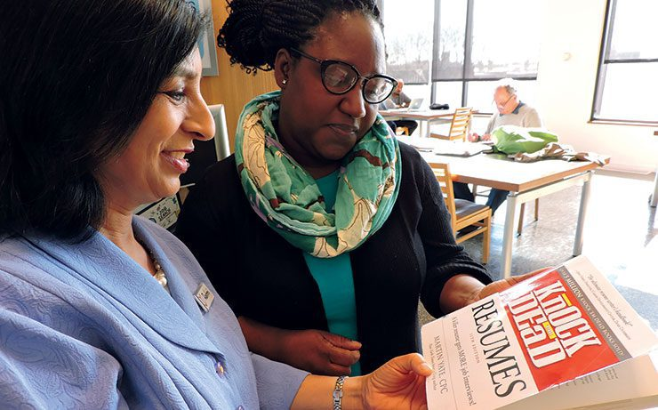 Librarian Rashmi Swain and Trina Wade look at Knock 'Em Dead Resumes