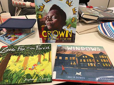 "Books displayed on a table: ""Crown: Ode to a Fresh Cut,"" ""Little Fox in the Forest,"" and ""Windows."""