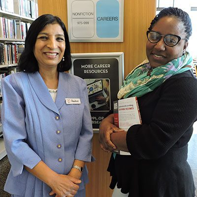 Adult Education and Job Seekers Librarian Rashmi Swain and Trina Wade pose in front of the Career Resources section.