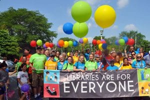 Library staff, board members, and friends holding Libraries Are for Everyone banner with balloons
