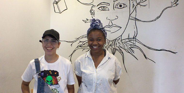 Teens posing in front of a mural in progress