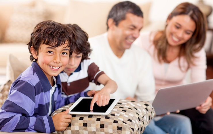 Family using a tablet and a laptop