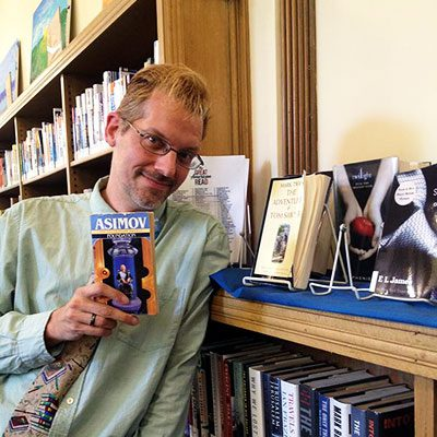 Adult and Teen Services Library Assistant Ben holds Foudation by Isaac Asimov