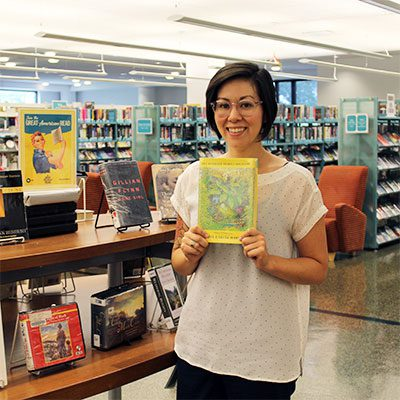 Adult and Teen Digital Learning Librarian Rose holds One Hundred Years of Solitude by Gabriel García Márquez