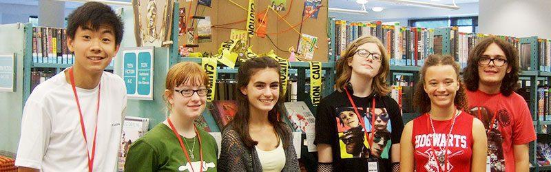 Group of teen volunteers in front of book display