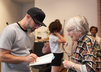 Kevin Coval signs book for Barbara Ballinger