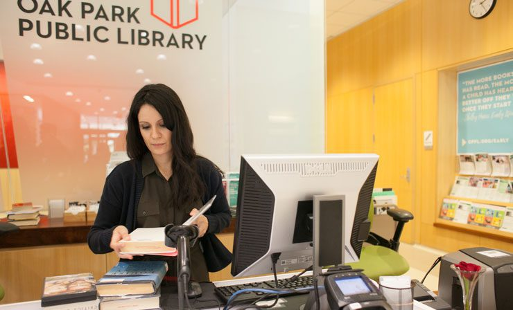 Library Assistant checks in books at the front desk of the Main Library