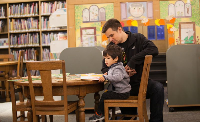Father and son reading at Maze Branch