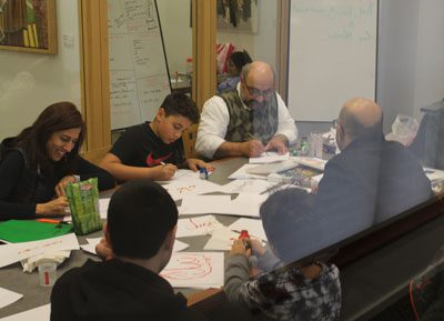 Adults and children around library conference room table