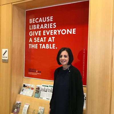 Julie in front of the Because libraries give everyone a seat at the table sign