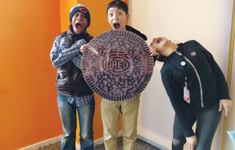 Three kids holding a giant cookie