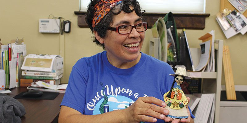 Kathy Valdivia, Multicultural Collection volunteer with artifact