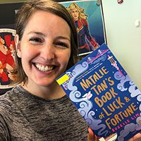 Jenna holding Natalie Tan's Book of Luck and Fortune