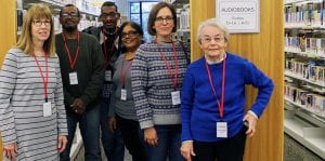 Library volunteers standing in the stacks