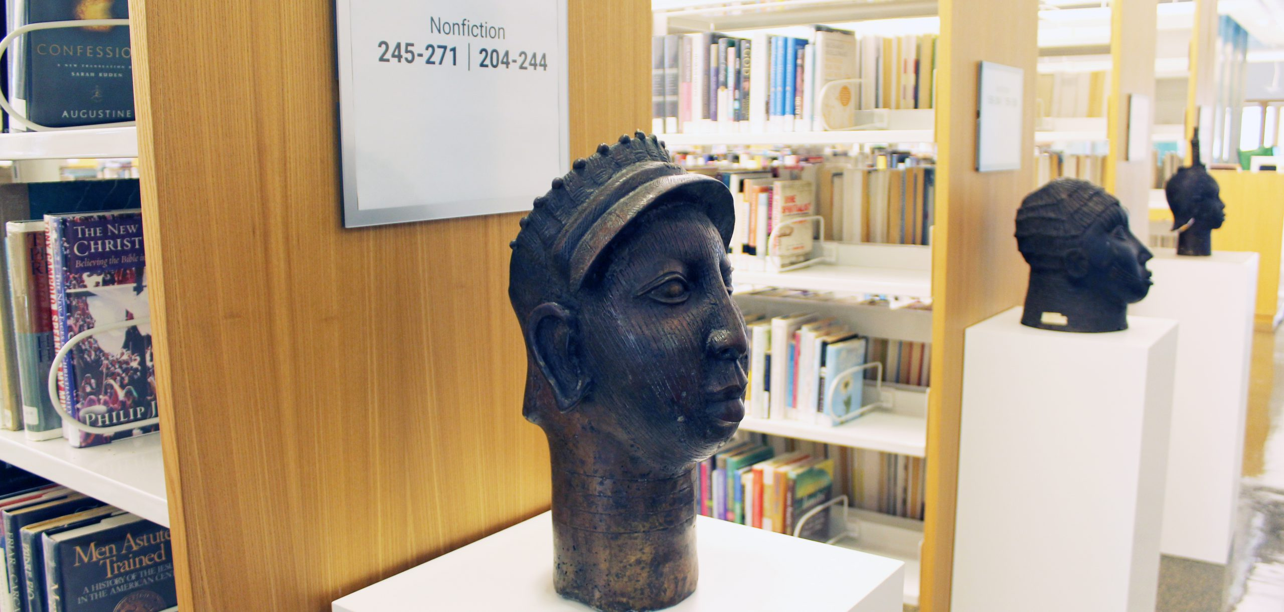 Sculptures on pedestals in front of bookshelves