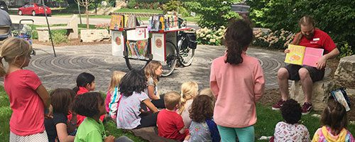 Children listening to a storytime from the Book Bike in the park
