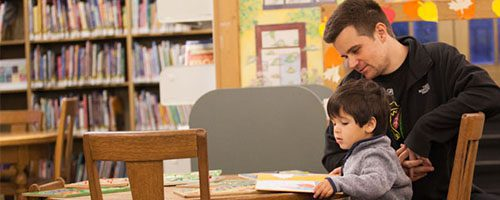Dad and son reading together at Maze Branch