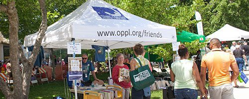 People visiting the Friends of the Library tent