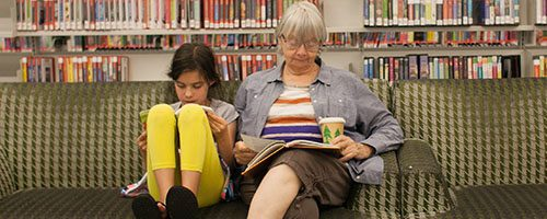 A girl and a woman reading on the couches at the library