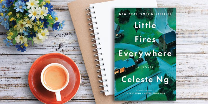 Little Fires Everywhere book on table with flowers, coffee mug, and notebook