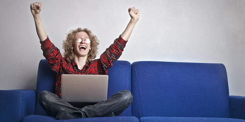 Excited person with hands up while using a laptop