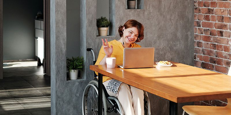 Person in wheelchair waiving at laptop