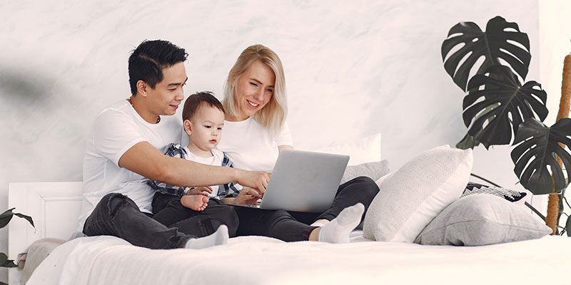 Family with baby looking at laptop