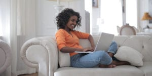 Woman on couch working on laptop