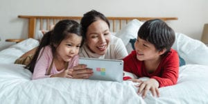 Parent and two kids with tablet on bed