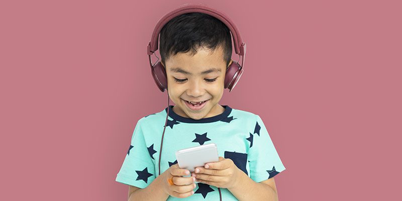 Kid with headphones listening to podcast