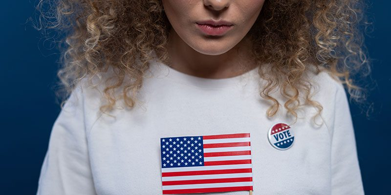 Person holding American flag and wearing vote button