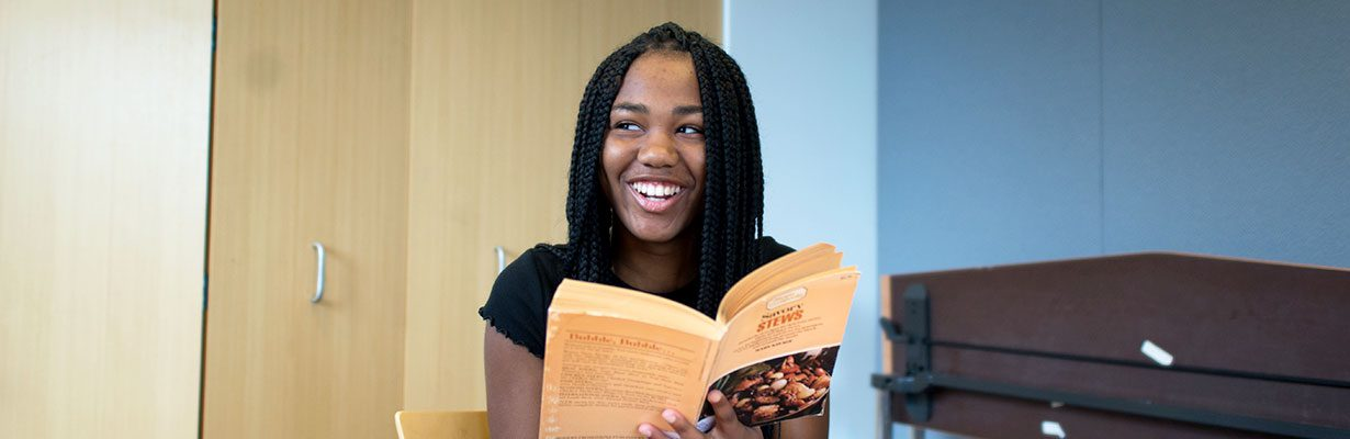 Teen holding book and laughing