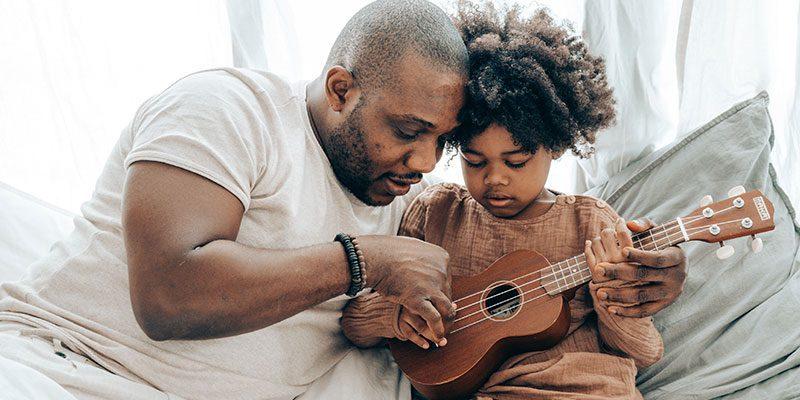 Child and adult playing ukulele
