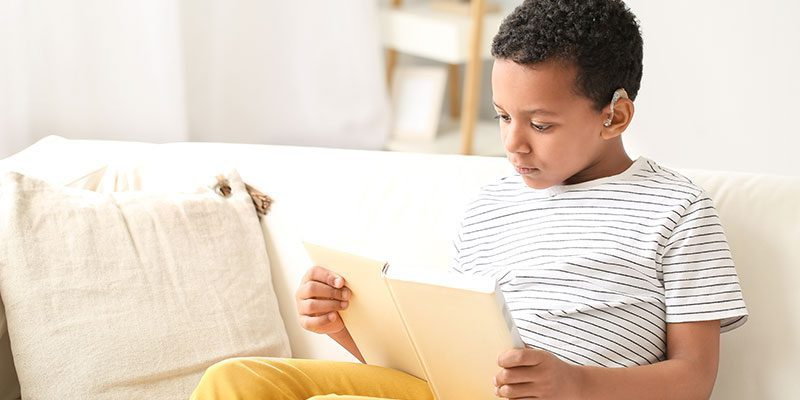 Child with hearing aide reading book