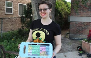 Shelley Harris holds an AAC (Augmentative and Alternative Communication) board in the Maze Branch Community Sensory Garden