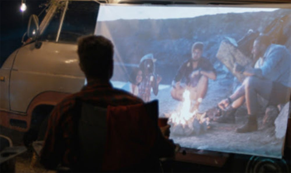 Person watching outdoor movie on LCD projector