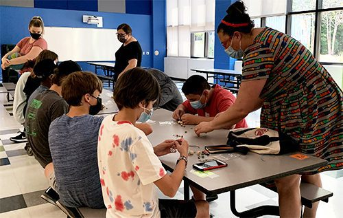 Teachers and students work on projects at table