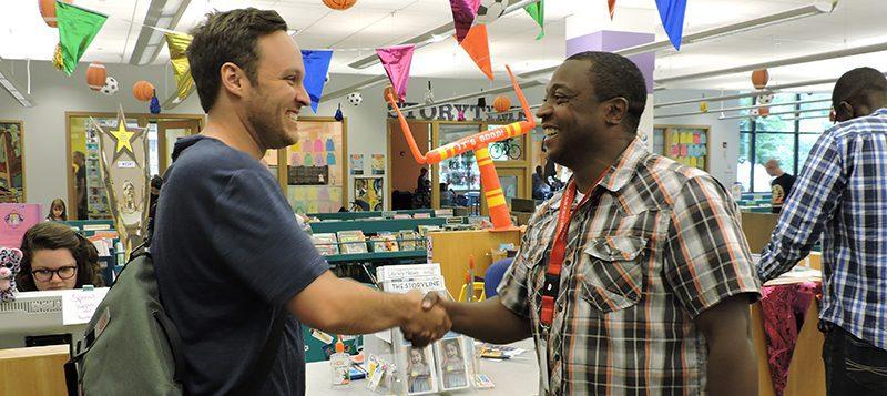 Holmes Elementary teacher Drew Finkbeiner and Oak Park Public Library's Robert Simmons shaking hands.