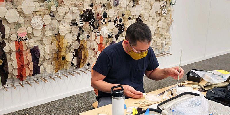 Artist works at table in front of artwork