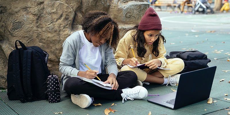 Two grade school students using a laptop to study outside